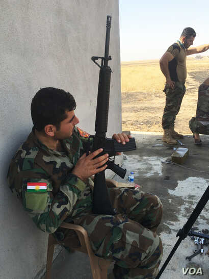 Iraqi Kurdish Peshmerga fighter outside a house recently recaptured from IS extremists on the Mosul frontline.