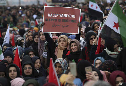 """Supporters of a pro-Islamic group stage a protest against the war in Aleppo, at the Bab al-Hawa border crossing with Syria near the southeastern city of Hatay, Turkey, Dec, 17, 2016. The placard reads in Turkish and Arabic: """"Aleppo is burning."""""""