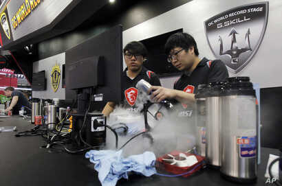 Competitors perform speed tests using dry ice to cool hardware at OC World Record Stage 2018 during the Computex Taipei, one of the world's largest IT expos, in Taipei, Taiwan, June 5, 2018.