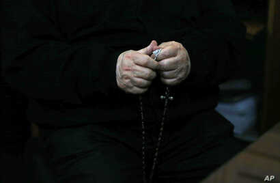 FILE - Rev. Fernando Karadima, Chile's most infamous pedophile priest, holds a rosary in court before testifying in a case that three of his victims brought against the country's Catholic Church in Santiago, Chile, Nov. 11, 2015.