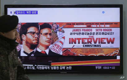 "FILE -A South Korean army soldier walks near a TV screen showing an advertisement of Sony Picture's ""The Interview,"" at the Seoul Railway Station in Seoul, South Korea, Dec. 22, 2014."