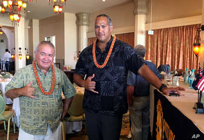 FILE - Richard Ha, left, and Keahi Warfield pose for a photo after a Rotary Club of Honolulu meeting, Aug. 16, 2016, where they gave a presentation about the educational benefits of the Thirty Meter Telescope project. They're part of the nonprofit or...