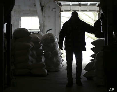 FILE - Richard McNulty of Sankey's Feed Mill walks through stacks of feed available at the store in Volant, Pa., April 5, 2018. McNulty said ground soybean is mixed in with certain livestock feeds. Many small U.S. manufacturers are feeling the impact...
