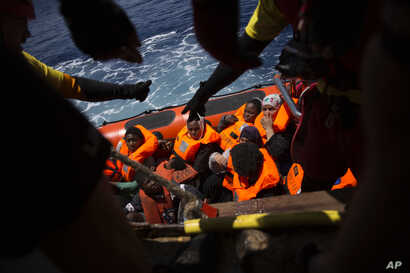 Women and children wait their turn to get on onboard the rescue vessel Golfo Azzurro by members of the Spanish NGO Proactiva Open Arms, after being rescued from a wooden boat sailing out of control in the Mediterranean Sea, about 18 miles north of Sa...