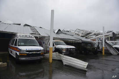 Rescue vehicles from the Emergency Management Agency stand trapped under an awning during the impact of Hurricane Maria, which hit the eastern region of the island, in Humacao, Puerto Rico, Sept. 20, 2017.