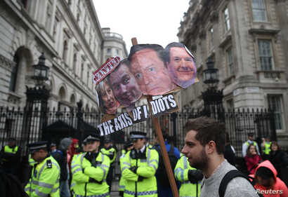 Demonstrators hold placards during a protest outside Downing Street in Whitehall, central London, Britain, April 9, 2016.