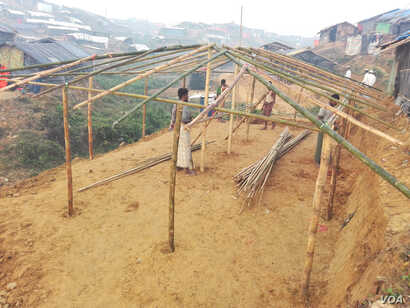 Some Rohingyas are building the structure of a house for a refugee family on the slope of a hill in Tengkhali refugee camp, Cox's Bazar, Bangladesh.