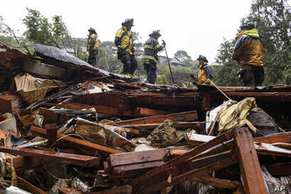 Southern Marin Fire Department members search a crushed house in the aftermath of a mudslide that destroyed three homes on a hillside in Sausalito, Calif., Feb. 14, 2019.
