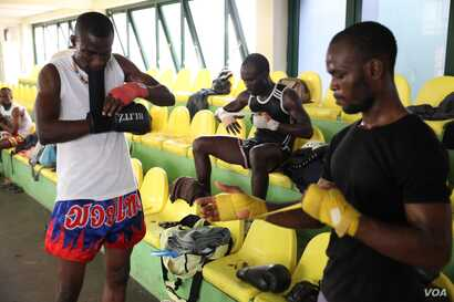 Kickboxers Isaac Aikins (left) and Isaac Commey Doku (center) ready for practice at the gym at a sport stadium near Accra, Ghana, Sept. 10. (Chris Stein/VOA)