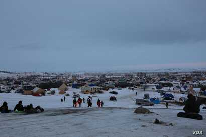 Thousands of people have camped on tribal land in protest of the Dakota Access oil pipeline (E. Sarai/VOA)