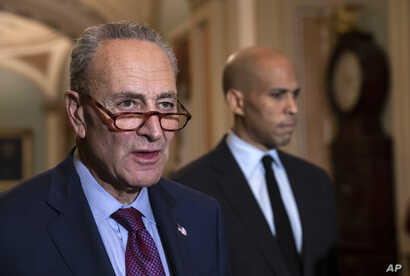 Senate Minority Leader Chuck Schumer, D-N.Y., with Sen. Cory Booker, D-N.J., at right, pauses as they speak to reporters about the political battle for confirmation of President Donald Trump's Supreme Court nominee, Brett Kavanaugh, following a close...
