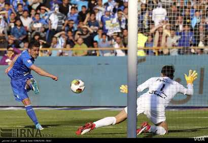 An Esteghlal player fires a shot against the Persepolis goalkeeper as two of Iran's fiercest rival football teams met at Azadi Stadium in Tehran, March 1, 2018.