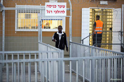 An African migrant walks outside the Holot open detention center in Israel's southern Negev desert, Sept. 22, 2014.