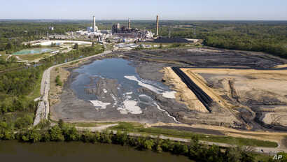 FILE -  the Richmond city skyline can be seen on the horizon behind the coal ash ponds along the James River near Dominion Energy's Chesterfield Power Station in Chester, Va.