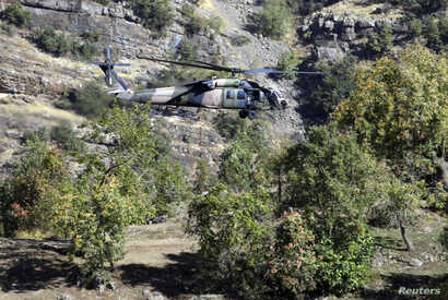 FILE - A Turkish military helicopter flies at low altitude along a mountain in Cukurca, near the Iraqi border in southeastern Turkey, where thousands of Turkish troops had launched a ground and air offensive against PKK fighters, Oct. 21, 2011.