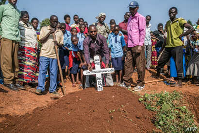 Mourners place a cross on the grave of Uwiringiyimana Gadi, 22, a victim of a collapsed mine, at the Ntunga public cemetery in Rwamagana, eastern Rwanda, on Jan. 22, 2019.