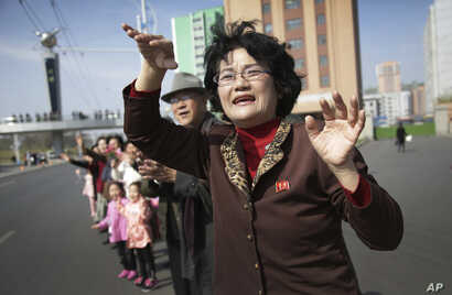 Sin Ye Suk, 50, a resident of Mirae Scientist Street stands in front of her apartment with fellow residents as they cheer on participants of the Pyongyang marathon, April 9, 2017, in Pyongyang, North Korea.