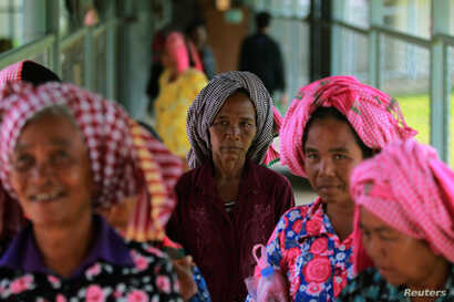 FILE - Women arrive at the entrance gate to the Extraordinary Chambers in the Courts of Cambodia (ECCC) for the trial hearing on evidences of forced marriage and rape during the Khmer Rouge regime, on the outskirts of Phnom Penh, Cambodia, Aug. 23, 2...