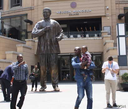 One of the places featured on the board of Monopoly Mzansi is Sandton Square, where a huge statue of Nelson Mandela is a major attraction. (D. Taylor for VOA)