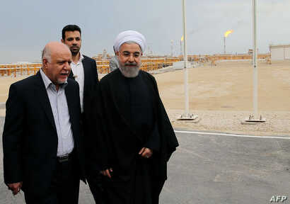 A handout picture released by the official website of the Iranian President Hassan Rouhani shows him (R) walking with Oil Minister Bijan Namdar Zanaganeh (L) at phase 12 of the South Pars gas field facilities in the southern Iranian port of Assaluyeh...