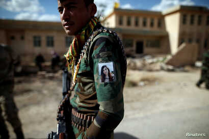Yazidi Popular Mobilisation Forces fighter Hussein Eisso hangs a photo of Nadia Murad, a Yazidi survivor and U.N. Goodwill Ambassador, on his arm in Kojo, Iraq June 1, 2017.