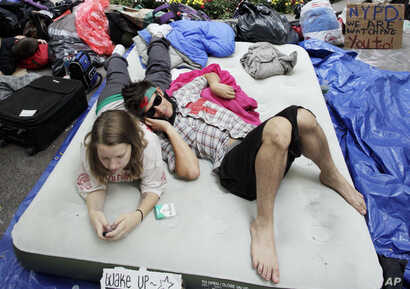 FILE - Robert Grodt, right, and Amber Oestreich, who are part of the protest movement Occupy Wall Street, rest on a mattress in New York's Zuccotti Park, Sept. 26, 2011.