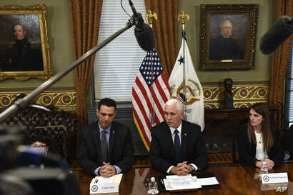 Vice President Mike Pence, center, sitting next to Carlos Anez, left, and Veronica Vadell Weggeman, right, speaks during a meeting in the Vice President's Ceremonial Office on the White House complex in Washington, with family members of the six Citg...