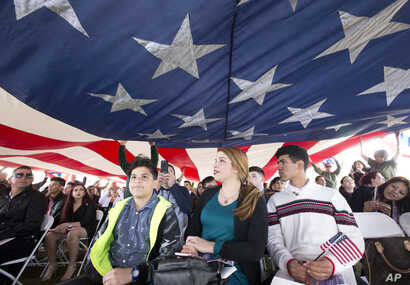 FILE - New citizens and their families look on as a large American flag is passed overhead during a U.S. Citizenship and Immigration Services naturalization ceremony, Jan. 19, 2018, in Biscayne National Park, Fla. Eighty-three children from 17 countr...