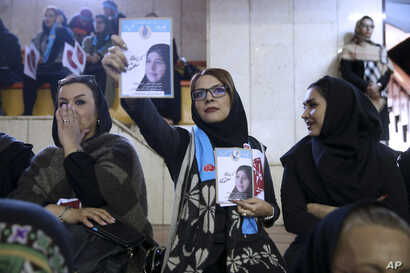 FILE - An Iranian woman holds leaflets showing Parvaneh Salahshouri, a candidate in parliamentary elections, during a reformists campaign rally in Tehran, Iran, Feb. 18, 2016.