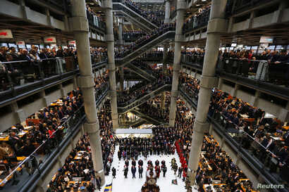 FILE - Lloyd's of London staff hold their annual Remembrance Day service at the Lloyd's building in the City of London, Britain, Nov. 11, 2015.