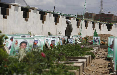 A Shi'ite rebel Houthi stands among the portrait adorned graves of  Houthi fighters and supporters who were killed in the ongoing conflict in Yemen, a few hours before the start of a fresh cease-fire, in Sana'a, Yemen, April 10, 2016.