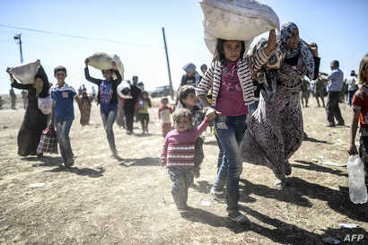 Syrian Kurds carry their belongings after they crossed the border between Syria and Turkey near the southeastern town of Suruc, Sanliurfa province, Turkey, Sept. 20, 2014.