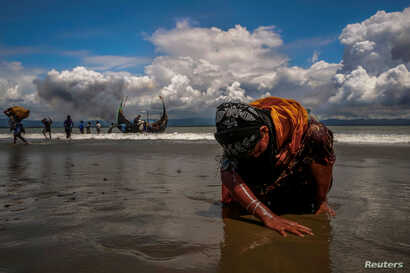 An exhausted Rohingya refugee woman touches the shore after crossing the Bangladesh-Myanmar border by boat through the Bay of Bengal, in Shah Porir Dwip, Bangladesh, Sept. 11, 2017.
