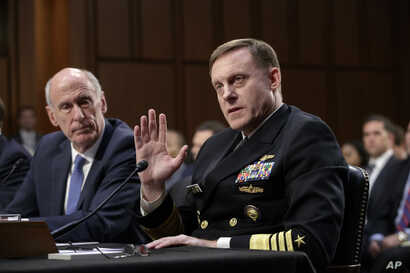 National Security Agency Director Adm. Mike Rogers, center joined by Director of National Intelligence Dan Coats, left, testifies before the Senate Select Committee on Intelligence about gathering intelligence on foreign agents, on Capitol Hill in Wa...