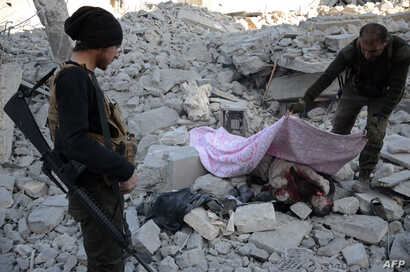 Turkish-backed Syrian rebels cover the body of an alleged Islamic State (IS) group fighter in the northwestern border town of al-Bab on February 23, 2017 after they fully captured the town from IS.