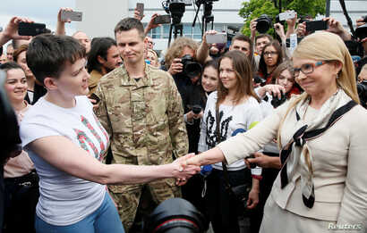 Ukrainian servicewoman Nadiya Savchenko shakes hands with Ukrainian former Prime Minister and leader of Batkivshchyna (Fatherland) party Yulia Tymoshenko at Boryspil International airport outside Kyiv, Ukraine, May 25, 2016.