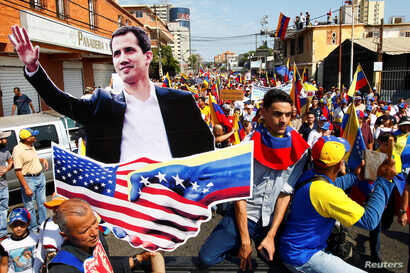 Opposition supporters carrying a cardboard cutout of Venezuelan opposition leader Juan Guaido take part in a rally against Venezuelan President Nicolas Maduro's government in Maracaibo, Venezuela, Feb. 12, 2019.