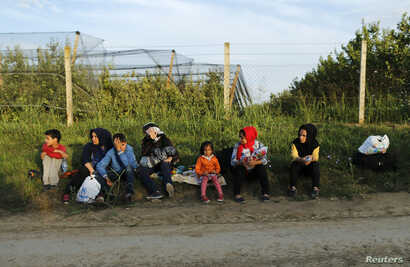 A group of migrants rest on the Serbian side of the border near Sid, Croatia September 16, 2015.
