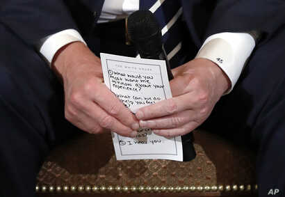 President Donald Trump holds notes during a listening session with students and teachers from Marjory Stoneman Douglas High School in Parkland, Florida, in the White House, Feb. 21, 2018.