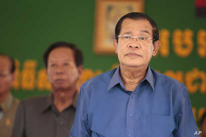 Cambodia's Prime Minister Hun Sen, right, prepares to deliver a speech during a factory visit outside of Phnom Penh, Cambodia,  Aug. 30, 2017.