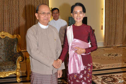 In this image provided by the Myanmar Ministry of Information, Myanmar President Thein Sein, left, shakes hands with opposition leader Aung San Suu Kyi during their meeting at the presidential in Naypyitaw, Myanmar, Dec. 2, 2015.