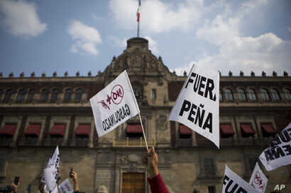 """People hold signs reading """"Pena out,"""" and """"No more gasoline price hikes"""" as they protest in front of the National Palace in Mexico City, Jan. 1, 2017."""