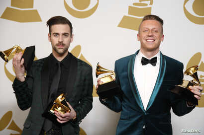 """Hip hop artists Macklemore (R) and Ryan Lewis pose backstage with their awards for Best New Artist, Best Rap Performance for """"Thrift Shop"""", Best Rap Song for """"Thrift Shop"""" and Best Rap Album for """"The Heist"""", Jan. 26, 2014."""