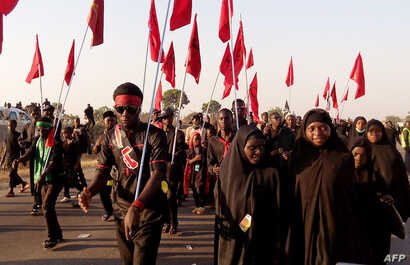 Shiite Muslims march during the 40th anniversary of the Ashura religious ceremony in the village of Dakasoye, northern Nigeria, following a suicide bombing attack that killed at least 21 people near Kano, Nov, 27, 2015.
