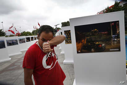 Savas Altay weeps as he visits an outdoor exhibition featuring photographs of July 15, 2016, coup attempt, in Istanbul, July 14, 2017. Turkey commemorates the anniversary with events honoring about 250 people who were killed while trying to oppose co...