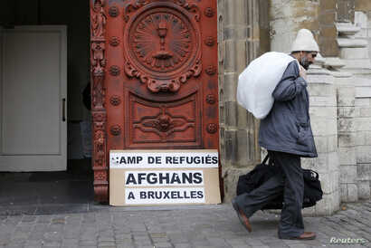 Asylum seeker Abdul Khaleq Homai, 51, from Herat, Afghanistan, walks out the Church of Saint John the Baptist at the Beguinage as he carries clothes to be washed outside the church in central Brussels January 30, 2014. Afghan asylum seekers have been...