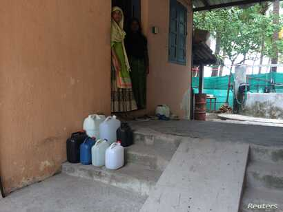 Kadeeja Lavanakkal (R) and her daughter Ruksana wait outside their home for the drinking water supply to start on Kavaratti island, the capital of India's Lakshadweep islands, May 6, 2018.