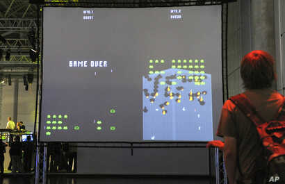 A visitor plays an adaption of the historic computer game 'Space Invaders' at the Games Convention in Leipzig, Germany, Aug. 20, 2008.