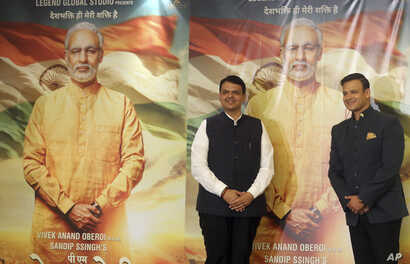 """FILE - Maharashtra state Chief Minister Devendra Fadnavis, left, and Bollywood actor Vivek Oberoi stand for photographs in front of posters of the now delayed film """"PM Narendra Modi,"""" in Mumbai, India, Jan. 7, 2019."""