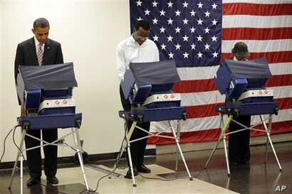 President Barack Obama (L) casts his vote during early voting in the 2012 election, at the Martin Luther King Community Center in Chicago, Illinois, October 25, 2012.
